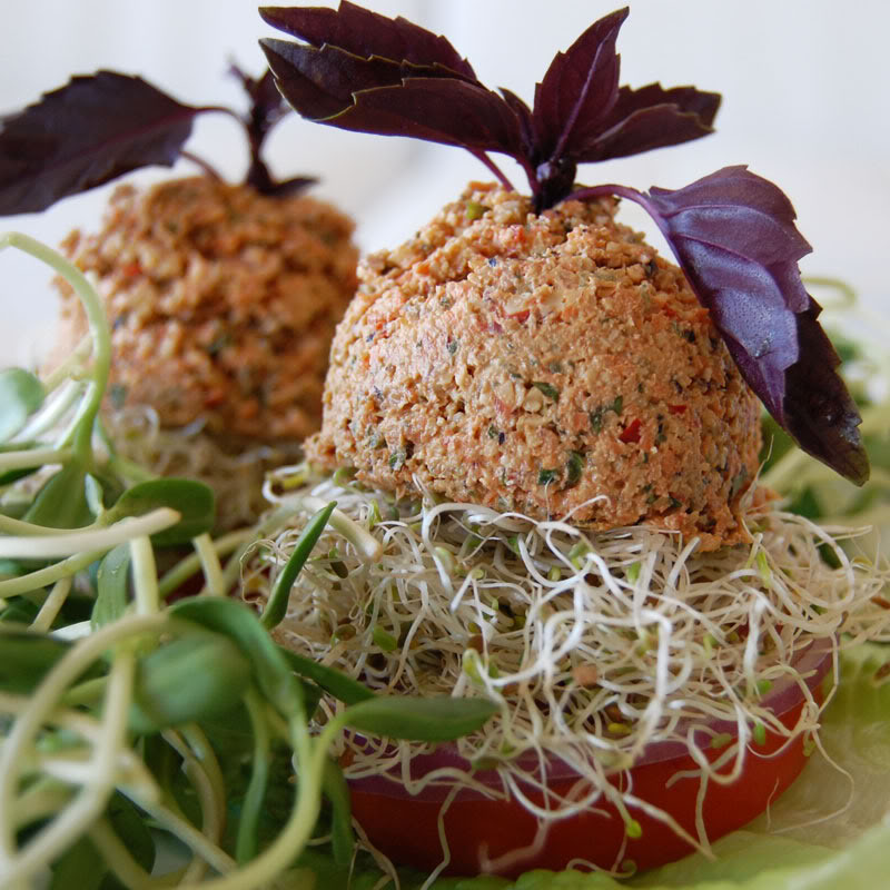 The Global Girl Raw Food Recipes: Raw Vegan Burger with a walnut patty and avocado, clover and sunflower sprouts in a tomato bun. This raw veggie burger is gluten free and oil free.