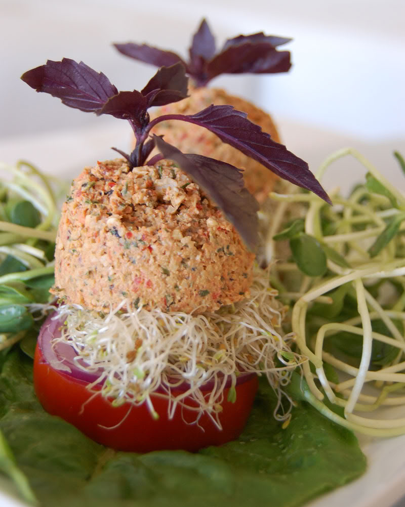 The Global Girl Raw Food Recipes: Raw Vegan Burger with a walnut patty and avocado, clover and sunflower sprouts in a tomato bun. This raw veggie burger is gluten free and oil free. width=