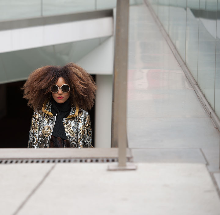 The Global Girl: Ndoema stars in a fashion editorial photographed by Paris-based photographer Kamel Lahmadi of Style and the City. Ndoema wears sunglasses by The Guise Archives, vintage silver and gold brocade coat, vintage gold chain and patent leather purse, Betsey Johnson gold glitter platform pumps, vintage black leather gloves, H&M gold metallic pants and vintage wool and fur scarf.