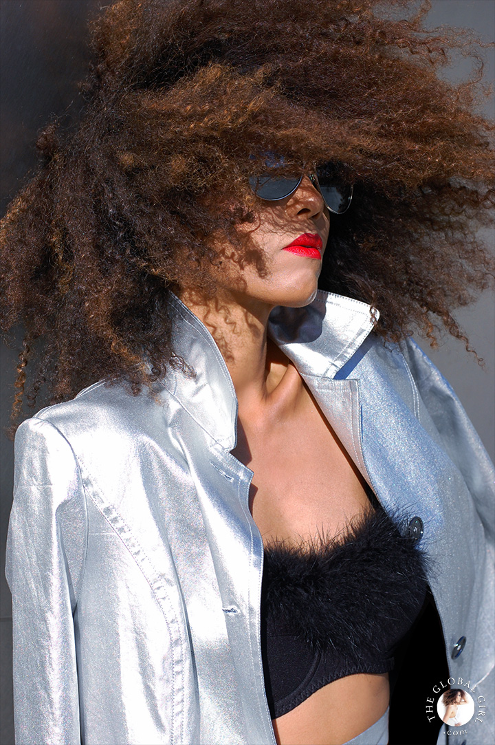 Ndoema rocks the metallic look in silver jacket, mirrored aviator sunglasses by Le Specs and feathered bra.