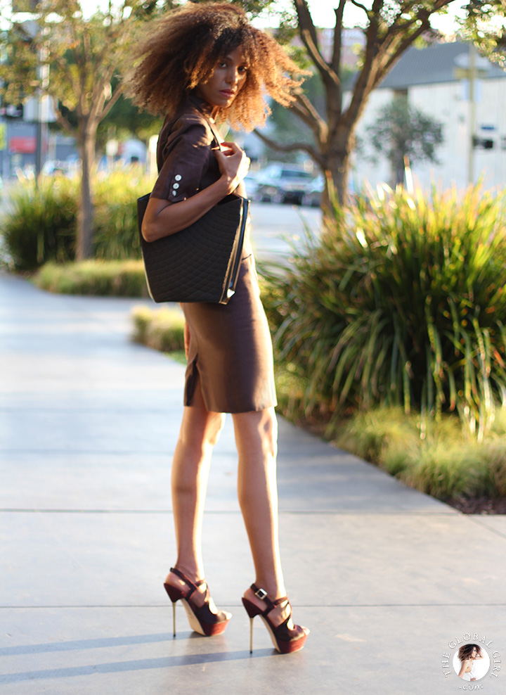 Ndoema is wearing a brown linen safari dress by Louis Féraud Paris   Vintage gold rim aviator sunglasses with graduated lens   Topshop metal heeled platform suede sandals   Quilted leather tote by Bally.