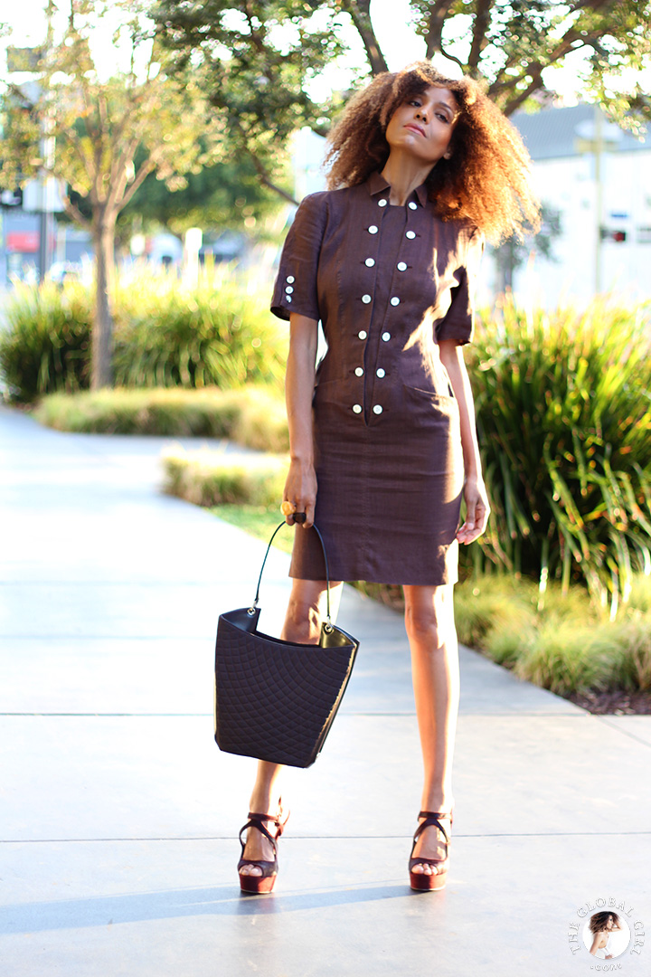 Ndoema is wearing a brown linen safari dress by Louis Féraud Paris | Vintage gold rim aviator sunglasses with graduated lens | Topshop metal heeled platform suede sandals | Quilted leather tote by Bally.