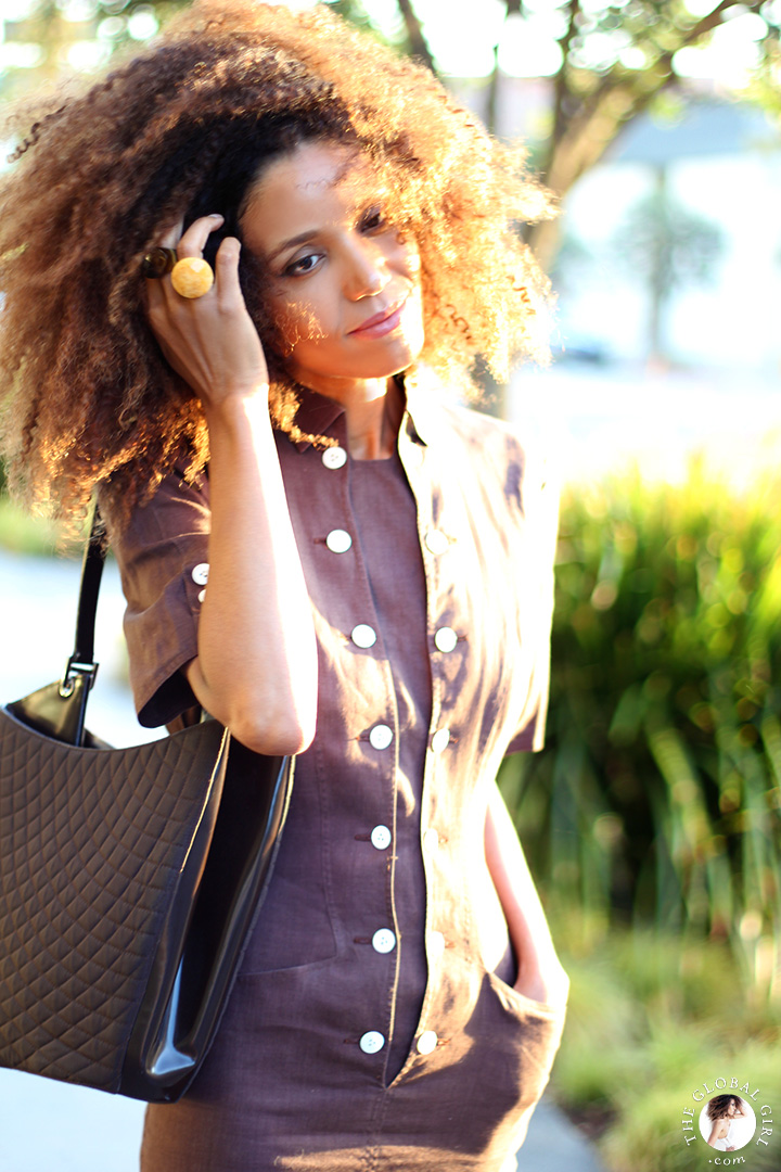 Ndoema is wearing a brown linen safari dress by Louis Féraud Paris and  quilted leather tote by Bally.