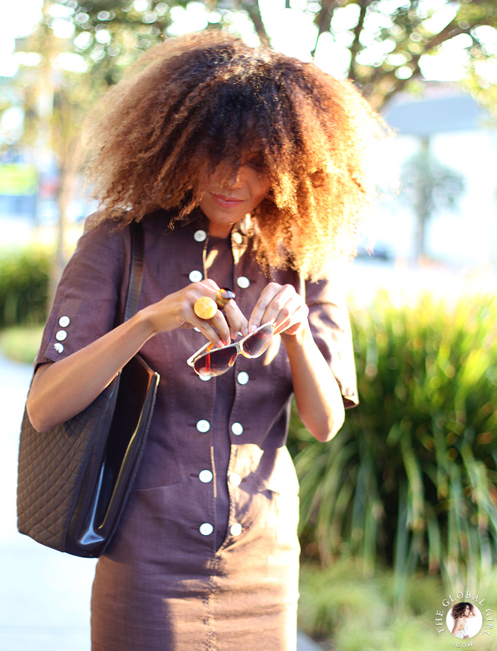 Ndoema is wearing a brown linen safari dress by Louis Féraud Paris   Vintage gold rim aviator sunglasses with graduated lens   Quilted leather tote by Bally.