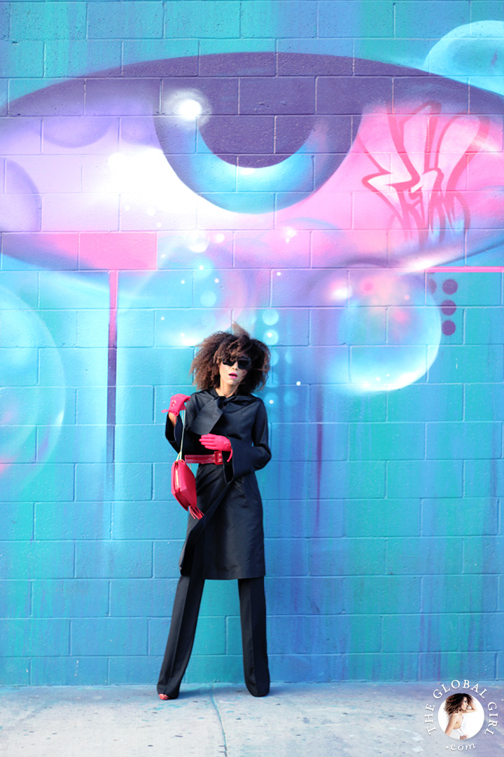 Ndoema dons a vintage silk coat and Balenciaga flare pants with Le Specs Craig and Karl x Le Specs 'Lost Weekend' sunglasses, Miu Miu red patent leather pumps, red patent leather belt by Betsey Johnson, Onna Ehrlich red crossbody bag and vintage red gloves.