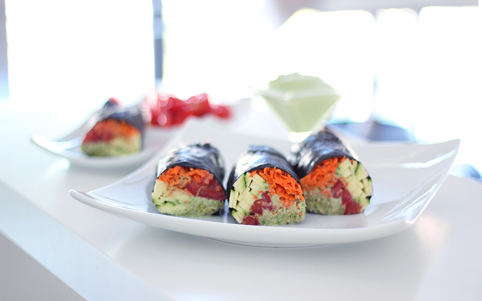 Raw vegan nori rolls with creamy cilantro sauce, shredded carrots, zucchini, tomatoes and clover sprouts. 100% gluten free, dairy free and oil free.