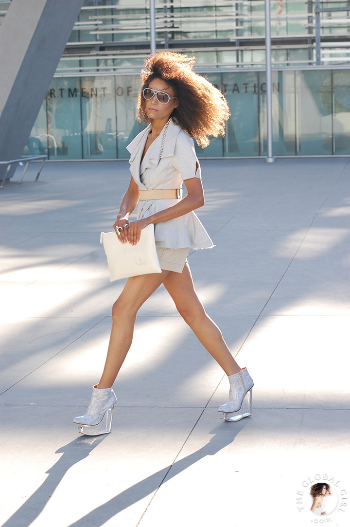 Ndoema rocks the chic women shorts suit look in a deconstructed jacket accessorized with aviator sunglasses, clear plastic heel platform shoes and white snake clutch.