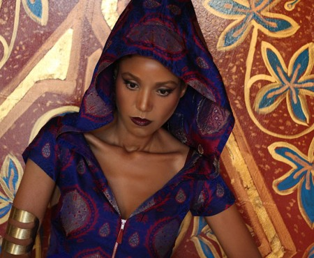 The Global Girl Editorials: Ndoema sports a silk hooded dress, tribal upper arm bracelet and pyramid studded two finger ring against vibrant gold Moroccan frescoes.