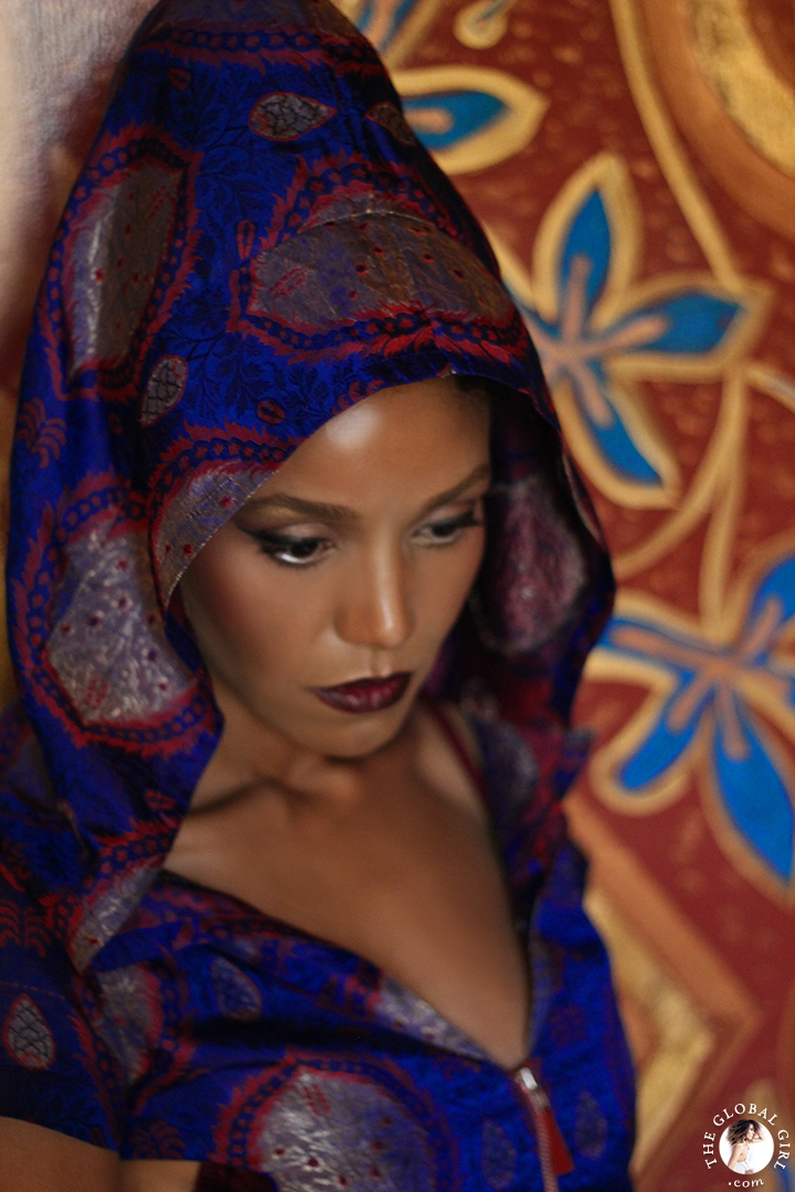 The Global Girl Editorials: Ndoema sports a silk hooded dress against vibrant gold Moroccan frescoes.