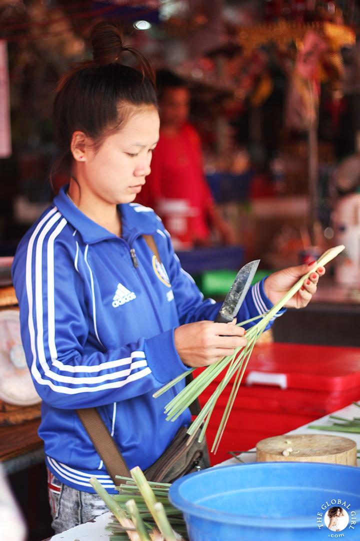 The Global Girl Travels: Street food merchant prepping lemongrass at Khlong Toey market in Bangkok, Thailand.