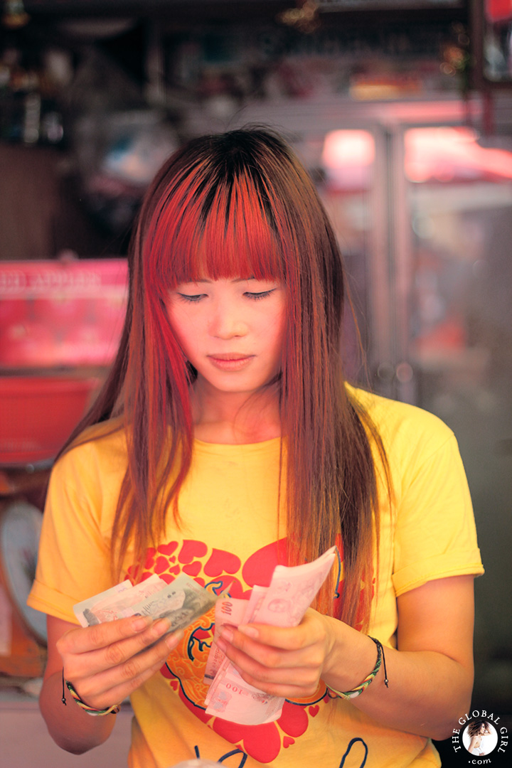 The Global Girl Travels: Beautiful Thai woman with red hair at Khlong Toey market in Bangkok, Thailand.