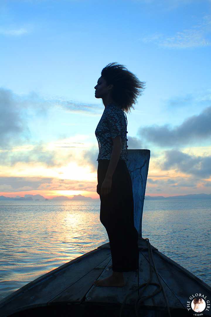 The Global Girl Travels: Ndoema takes in the sunrise on a traditional thai long boat in the Andaman Sea.