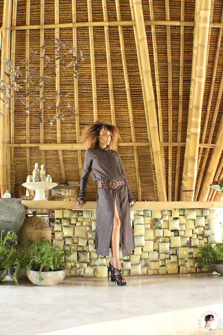 The Global Girl Travels: Ndoema in a Dries Van Noten linen maxi shirt dress with braided leather belt and sterling silver & smoky quartz bracelet amidst modern bamboo architecture at Glamping Hub 's luxury safari tents in Ubud, Bali.