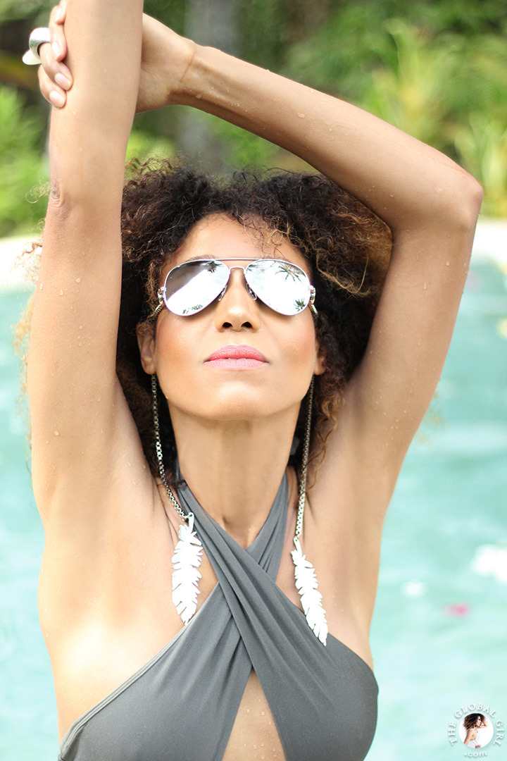 The Global Girl Travels: Ndoema lounges poolside in a cross halter one-piece swimsuit and aviator silver mirrored sunglasses at Glamping Hub's eco-chic tents in Ubud, Bali. The suite's private jungle-flanked infinity pool provides utmost serenity.