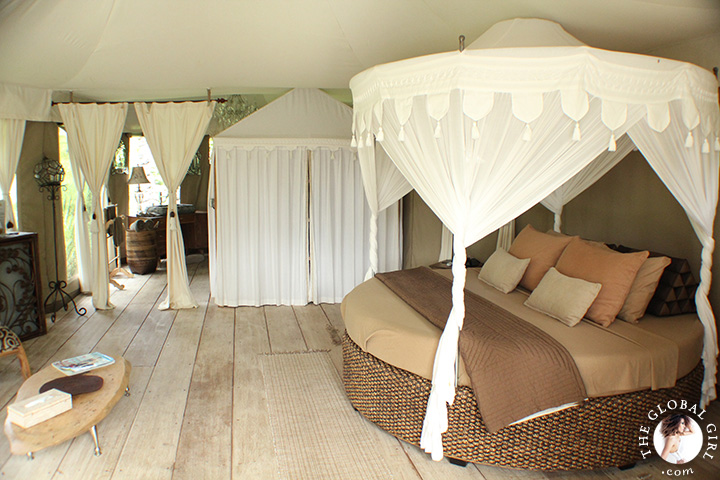 The Global Girl Travels: Tenda Penjor, a luxury safari-themed eco-chic glamping tent in Ubud, Bali. Featuring beautiful rattan canopy bed with tassel curtains and eco-friendly wood furniture by local Balinese artists and artisans.