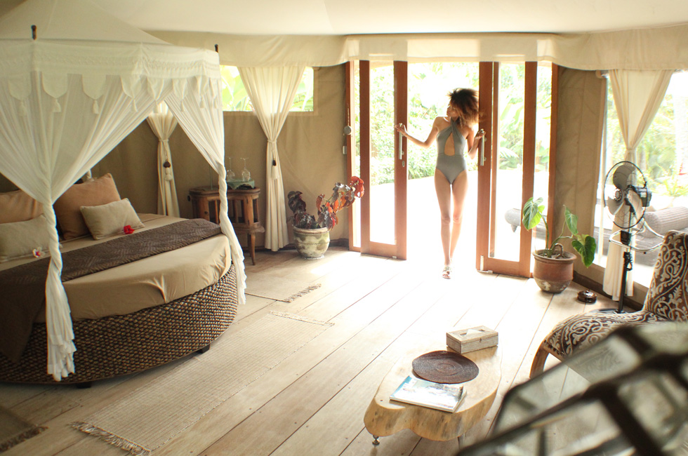 The Global Girl Travels: Ndoema at Tenda Penjor, a luxury safari-themed eco-chic glamping tent in Ubud, Bali. Featuring beautiful rattan canopy bed with tassel curtains and eco-friendly wood furniture by local Balinese artists and artisans.