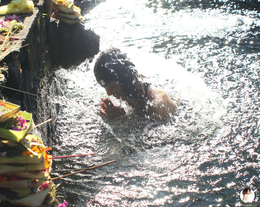 The Global Girl Travels: Ndoema bathing in holy spring water at the Tirta Empul Temple in Bali, Indonesia.