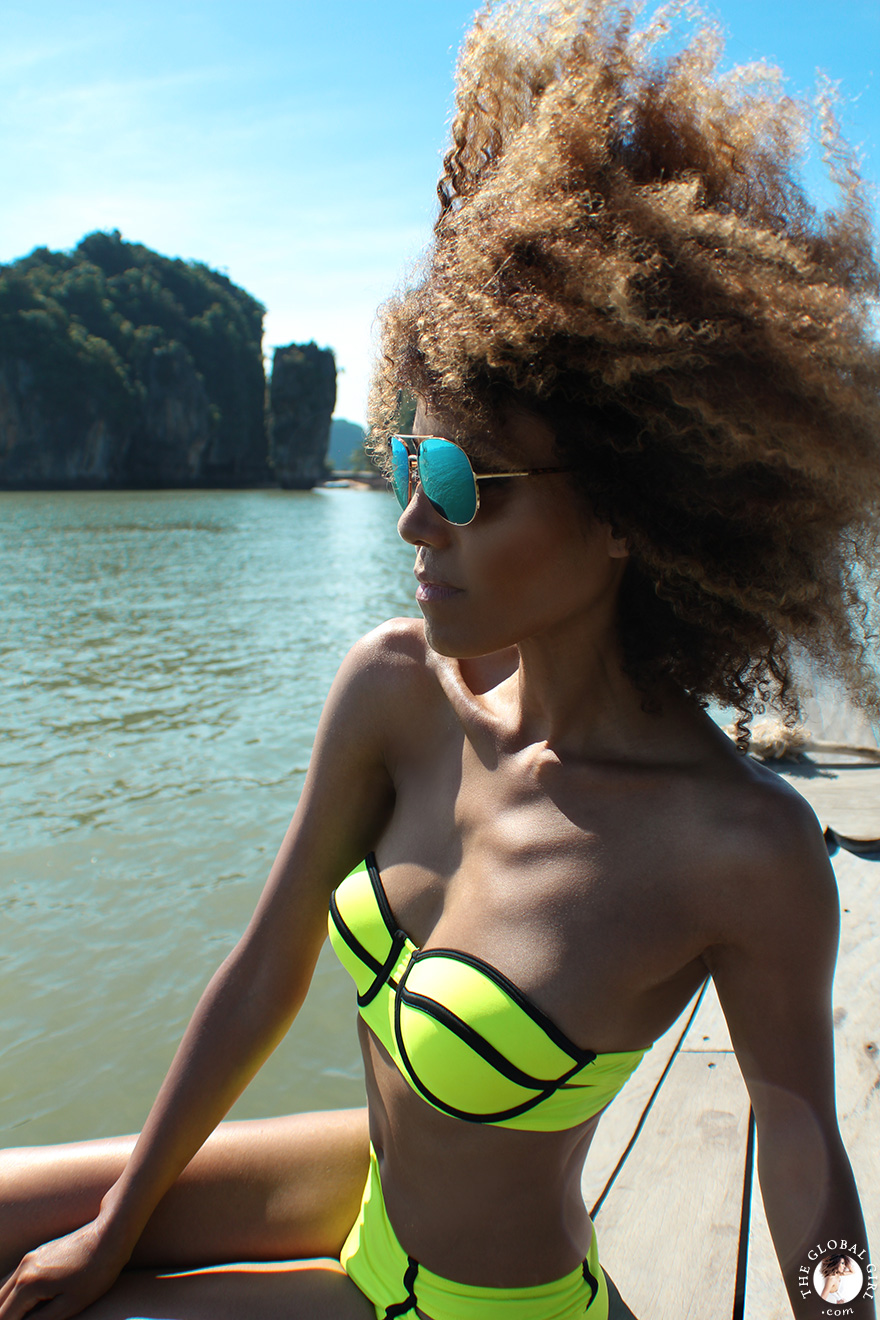 The Global Girl Travels: Ndoema sports a contrast neon bikini with mirrored aviator sunglasses while sailing off James Bond Island in Phang Nga Bay, Thailand.