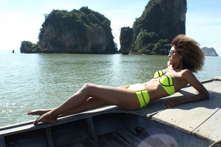 The Global Girl Travels: Ndoema sports a contrast neon bikini with mirrored aviator sunglasses while sailing off James Bond Island in Phang Nga Bay, Thailand.