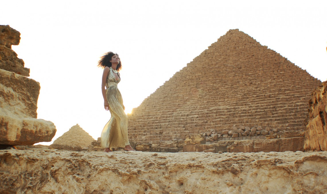 The Global Girl Travels: Ndoema in a goddess gold lame gown by Vicky Tiel at the Giza Pyramids in Egypt.