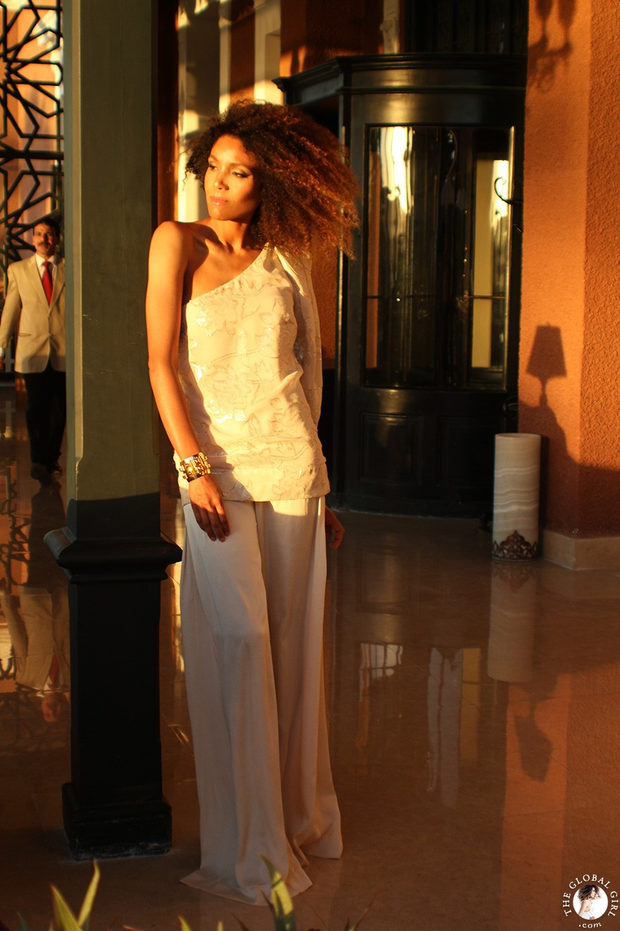 The Global Girl Travels: Ndoema sports a beige on beige one shoulder silk blouse with silk palazzo wide leg pants and gold pyramid cuff at the The Sofitel Legend Old Cataract Hotel in Aswan, Egypt.