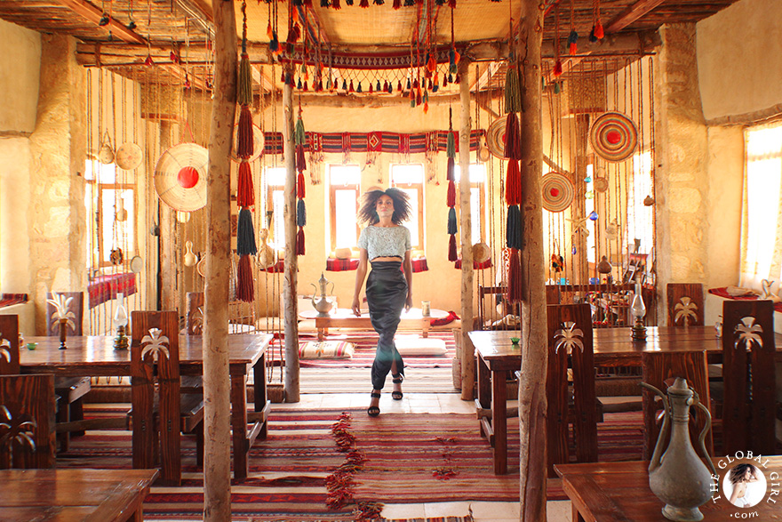The Global Girl Travels: Ndoema at Talist, a Berber-style luxury and eco-friendly resort at Siwa Oasis, Egypt. Ndoema sports a high-waist maxi skirt by Vivienne Westwood with a vintage embellished cropped top and jeweled stiletto heels.