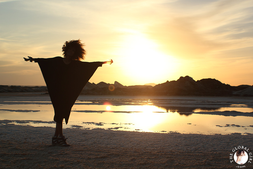 The Global Girl Travels: Ndoema at a local salt mine against the blazing North African sunset, at Siwa Oasis, Egypt.