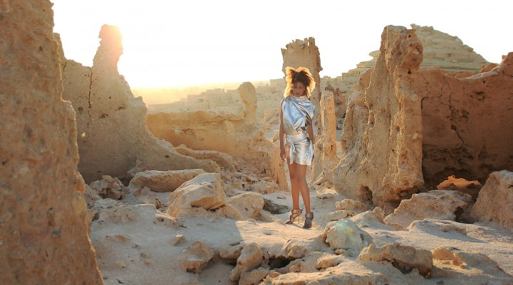 The Global Girl Fashion Editorials: Ndoema goes futuristic in a silver metallic dress against the ancient ruins of Shali Ghadi, a spectacular 13th-century fortress at Siwa Oasis, Egypt.
