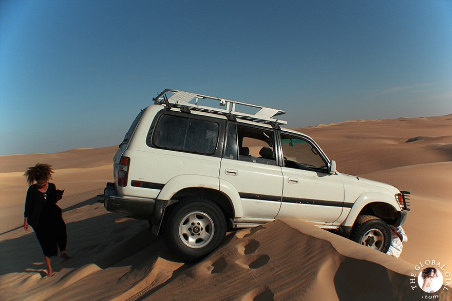 The Global Girl Travels: Four-wheel drive land cruiser stuck on a sand dune in the Libyan desert on a safari in the sahara, North Africa.