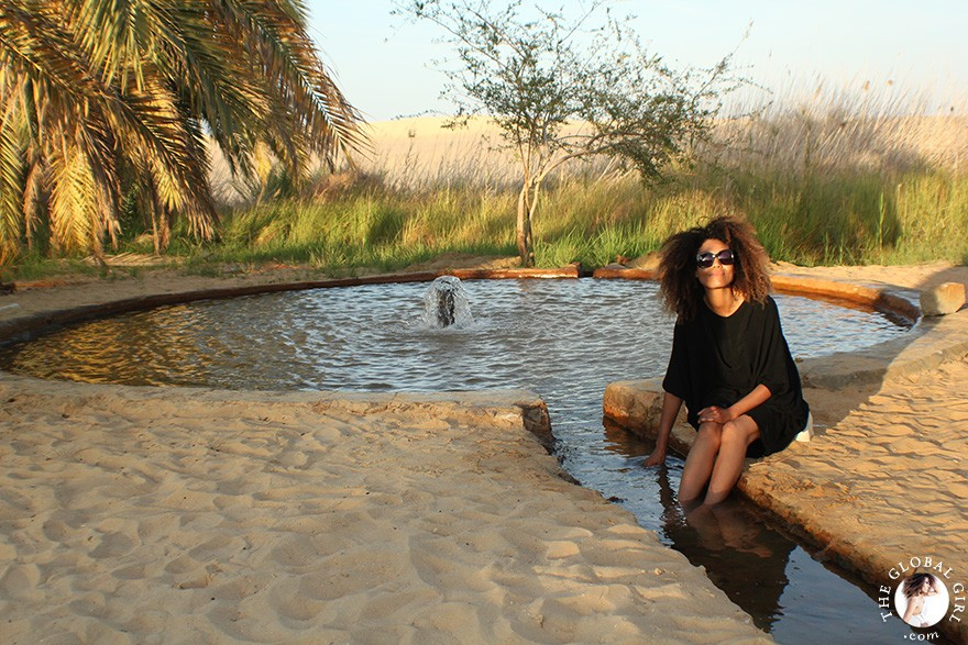 The Global Girl Travels: Ndoema soaking in the healing sulfur natural springs at the beautiful freshwater lake at Bir Wahed, a striking natural landmark on the edge of the Great Sand Sea, a 72,000 km² sand desert region in North Africa stretching between western Egypt and eastern Libya.