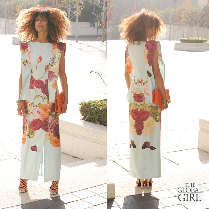 Ndoema wears a head-to-toe floral print look in a maxi dress with front slit by Mimi Plange and floral-print sandals by Report Signature with a vintage orange satin clutch, custom turquoise and brass oversized bracelet, and yellow agate ring.
