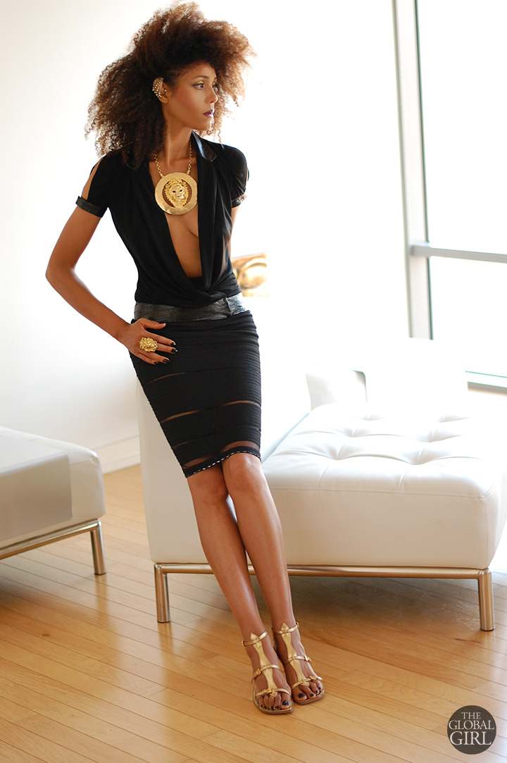 The Global Girl Daily Style: Ndoema rocks the black and gold look in a Versace pencil skirt and Richard Tyler Couture top with plunging neckline and cutout sleeve, accessorized with gold oversized lion necklace, gold lion ring and gold fan ear cuff with gladiator sandals by Sigerson Morrison
