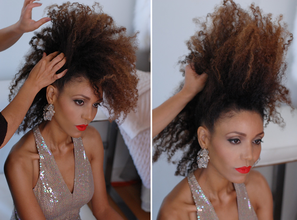 The Global Girl Cinema Series: Ndoema gets ready for the red carpet premiere of her new fashion film. She sports her trademark natural hair in a statement-making mohawk to contrast her classic cat eye and red lip look.