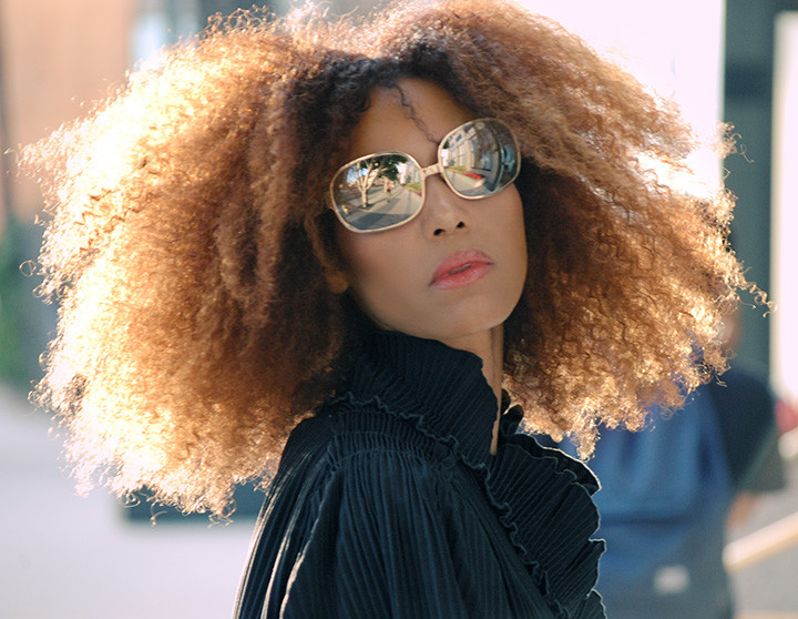 The Global Girl Daily Style: Ndoema sports her trademark mane of natural curls Christian Roth mirrored sunglasses.