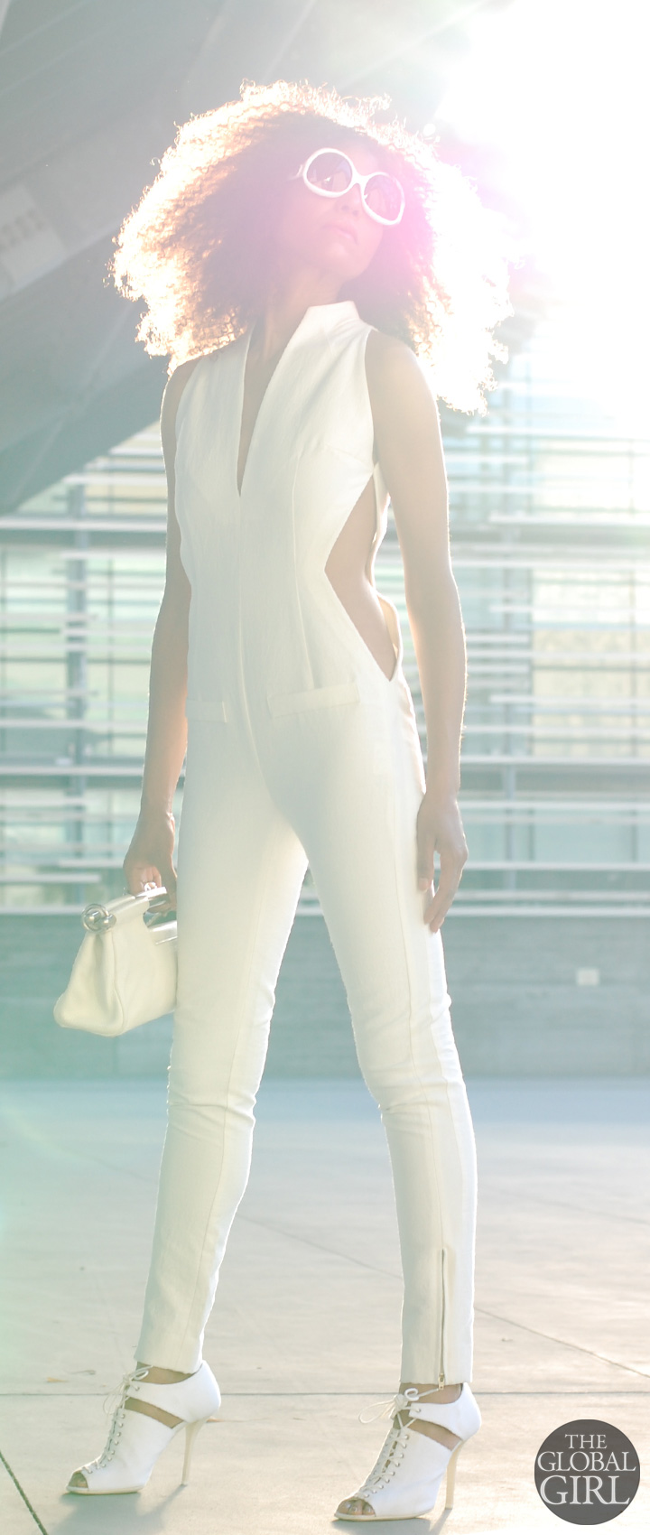 Ndoema channels Sun Girl Selah Burke in all white look: cutout jumpsuit from Son Jung Wang Spring 2014 runway collection | White frame oversized sunglasses by Balenciaga | White cutout lace-up sandals by Helmut Lang | White leather bag by Prada.