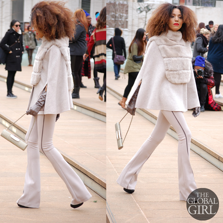 The Global Girl Style: Ndoema rocks the winter cape look in a beige Son Jung Wan cape and flare pants ensemble with Sergio Rossi bag during New York Fashion Week Fall 2014.
